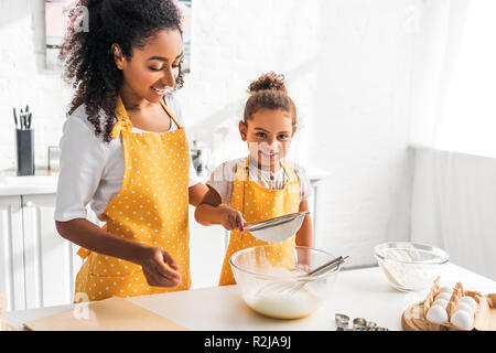 happy african american mother and daughter preparing dough and sieving flour together in kitchen - Stock Photo