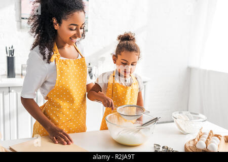 cheerful african american mother and daughter preparing dough and sieving flour in kitchen - Stock Photo