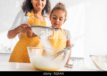 cropped image of african american mother and daughter preparing dough and sieving flour in kitchen - Stock Photo