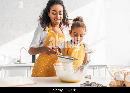 african american mother helping daughter preparing dough and sieving flour in kitchen - Stock Photo