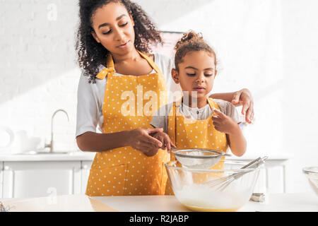 african american mother and daughter preparing dough and sieving flour together in kitchen - Stock Photo