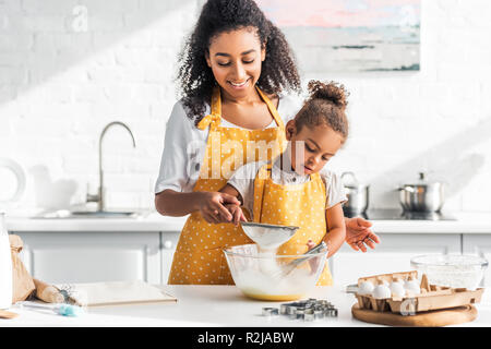 smiling african american mother and daughter preparing dough and sieving flour in kitchen - Stock Photo