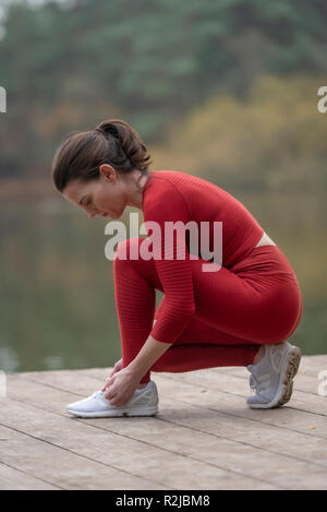 female jogger tying up her shoes before running - Stock Photo
