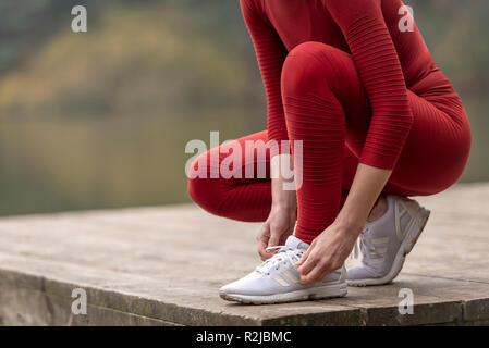 close up of a female jogger tying up her shoes before running - Stock Photo