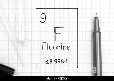 The Periodic table of elements. Handwriting chemical element Fluorine F with black pen, test tube and pipette. Close-up. - Stock Photo