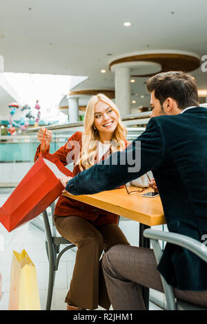 smiling woman showing something in shopping bag to boyfriend while sitting in cafe in shopping center - Stock Photo