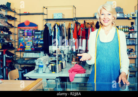 cheerful smiling mature woman standing in sewing studio ready to take order - Stock Photo