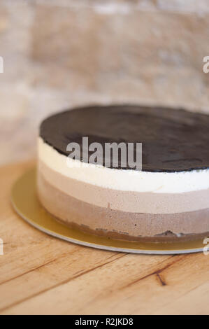 Three color chocolate mousse cake on wooden background - Stock Photo