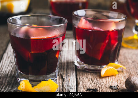 Christmas hot drinks with citrus fruits and spices on rustic wooden table, festive cozy winter holiday, mulled wine in glasses - Stock Photo