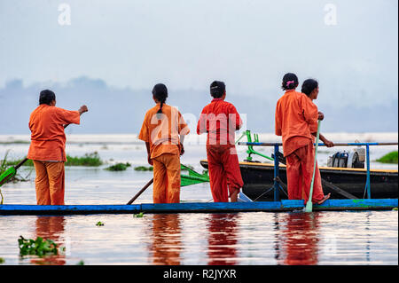 Women getting ready to practice boat racing on Inle Lake in preparation for the Phaung Daw Oo Festival in October. Shan State Myanmar - Stock Photo