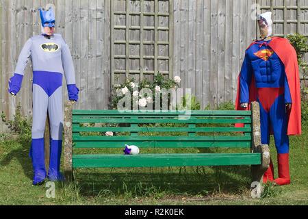 Batman and superman scarecrows in a garden - Stock Photo