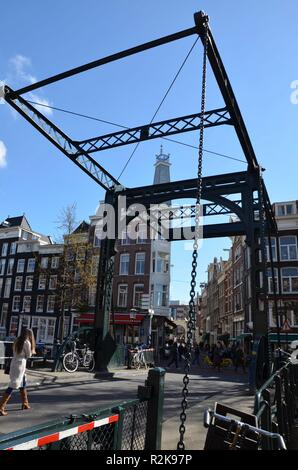 Closeup of a draw bridge over a canal in Amsterdam, traditional canal houses in the background, people are walking around, bicycles - Stock Photo