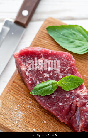 Raw meat with marinated salt, pepper and Basil seasoning leaf. Morning in the kitchen. Raw fresh beef steak on a wood cutting board. White wooden background, top view, copy space, Daylight