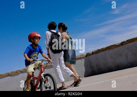 A young boy on a bike in the sunshine with crash hat, helmet on by the Spanish coast. - Stock Photo