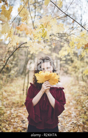 Beautiful girl with curly dark hair in a marron silk top in an autumn park, smiling at the camera and holding maple leaves in front of her face - Stock Photo