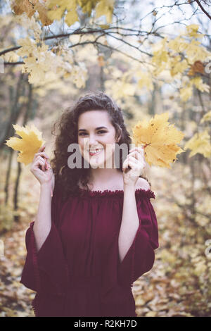Beautiful girl with curly dark hair in a marron top in an autumn park, smiling at the camera and holding maple leaves - Stock Photo