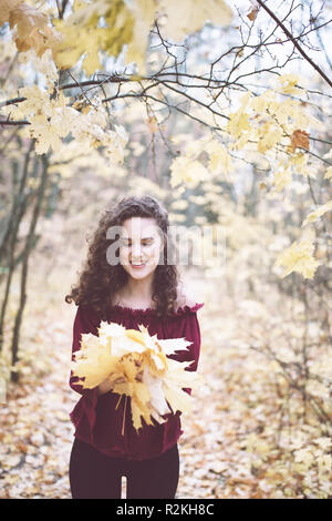 Beautiful girl with curly dark hair in a marron top in an autumn park holding maple leaves and smiling - Stock Photo