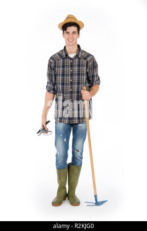 Young farmer with shears and hoe in hands, he is wearing a straw hat, checked shirt and green rubber boots - Stock Photo