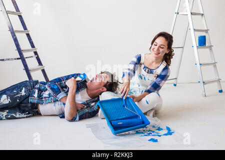 Smiling loving couple doing home renovations, the woman is holding a paint roller and young man is resting. - Stock Photo