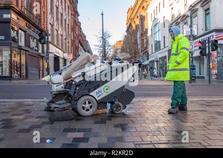 A male Council street cleaner wearing a Hi Vis Jacket and a hoodie using the Maxvac Maxwind pavement sweeper on Sauchiehall St, Glasgow, Scotland, UK - Stock Photo