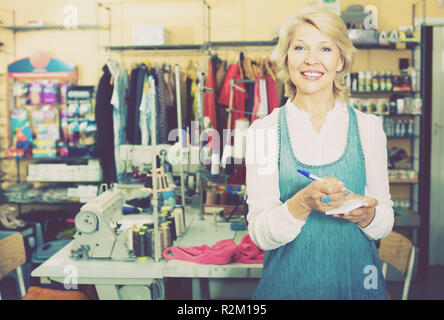 cheerful smiling mature woman tailor standing in sewing studio ready to take order - Stock Photo