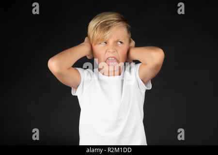 Little blond boy covers his ears and sticks out his tongue - Stock Photo