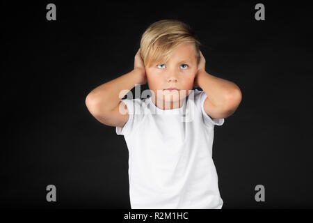 Little blond boy covers his ears - Stock Photo