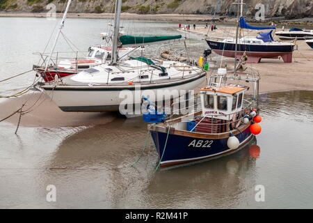 A small lobster fishing vessel is moored up at low tide, New Quay, wales, Ceredigion - Stock Photo