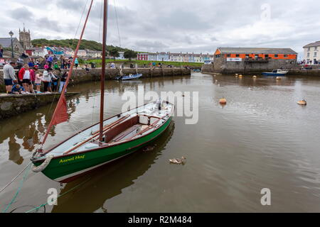 An empty boat stands moored up in the inner harbour in the Coastal town of Aberaeron, while people fish off the quayside for crabs - Stock Photo