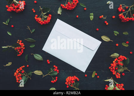 Flat lay white blank envelope mock up copy space on dark desktop background decorated with wild berry fruit arrangement - Stock Photo