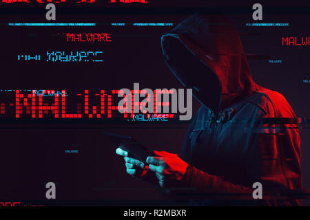 Malware concept with faceless hooded male person using tablet computer, low key red and blue lit image and digital glitch effect - Stock Photo