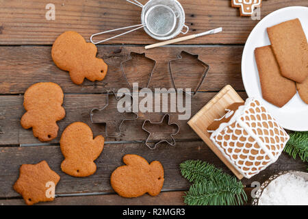 Blank biscuit gingerbread, ready to decorate. Icing of Christmas bakery. Woman decorating honey gingerbread cookies on wooden brown table. closeup, copy space - Stock Photo