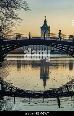 Bridge over lake with jogger reflection on water underneath and castle Charlottenburg in the background