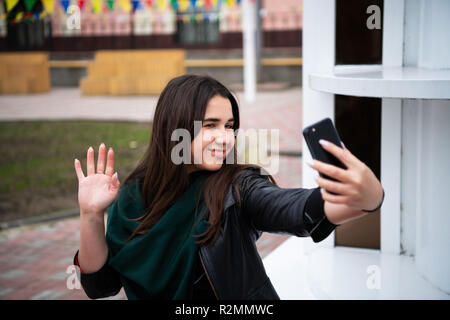 Smiling teen girl waving hand looking at phone camera, happy young lady making video call at home, greeting online by video call or recording videoblog, saying hello starting broadcast - Stock Photo