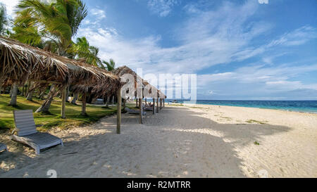 Sun beds on the beach under thatched roofs by the sea, Fiji - Stock Photo