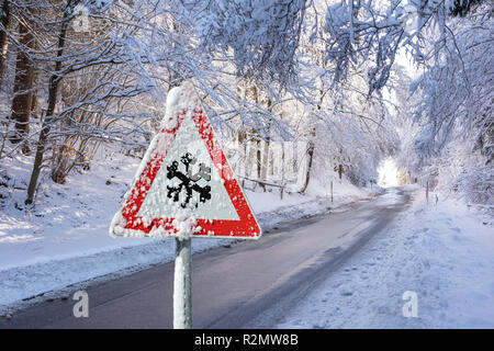 Warning sign in front of snow on rural road - Stock Photo