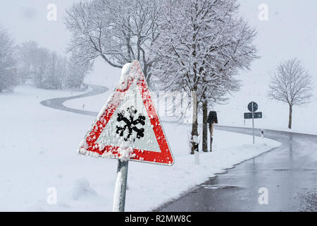 Warning sign of hard-packed snow on road - Stock Photo