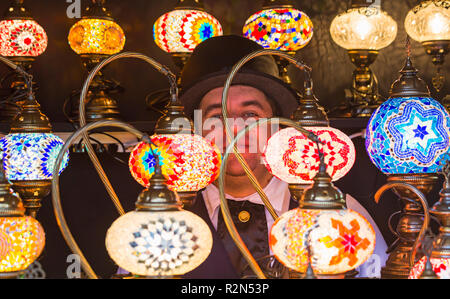 Gloucester, Gloucestershire, UK. 19th Nov, 2018. Gloucester Quays award winning Victorian Christmas Market, the biggest free entry Victorian Christmas Market in the South West. Market stall holder peering through colourful decorative lights lamps for sale.  Credit: Carolyn Jenkins/Alamy Live News - Stock Photo