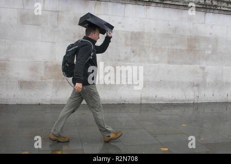 London UK. 20th November 2018. Pedestrians shelter under umbrellas from the cold freezing rain in Trafalgar Square London Credit: amer ghazzal/Alamy Live News - Stock Photo