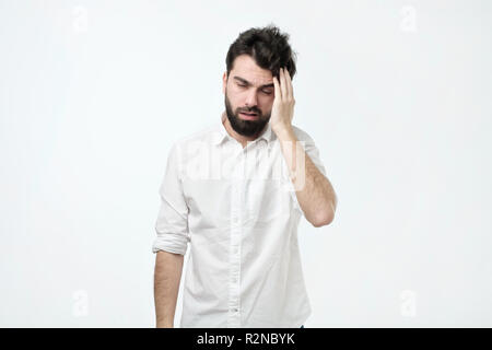 Bearded man with messy hair and beard, rubbing head and being tired or having hangover - Stock Photo