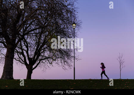 Person training. Woman running or jogging in a park at night, Nottingham, England, UK - Stock Photo