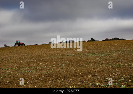 A farmer tills a field on a hill in Lower Sheering Essex.  Late autumn and rain is expected. - Stock Photo