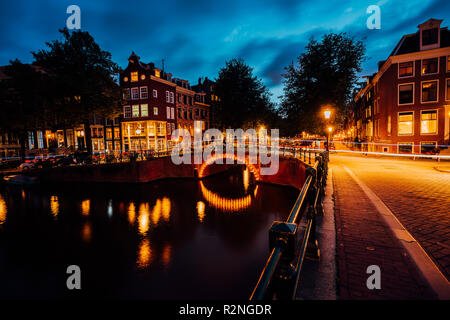 Amazing night in Amsterdam. Illuminated canal and bridge with typical dutch houses and bicycles, Holland, Netherlands. Lights trails from the bicycles. Long exposure - Stock Photo