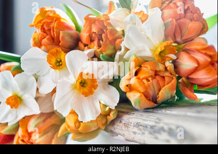 Bouquet of tulips and daffodils on a windowsill - Stock Photo