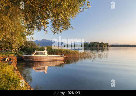 Boat on the Chiemsee in front of Chiemgau Alps with Kampenwand, Fraueninsel, Frauenchiemsee, Chiemsee, Chiemgau, Upper Bavaria, Bavaria, southern Germany, Germany, Europe - Stock Photo
