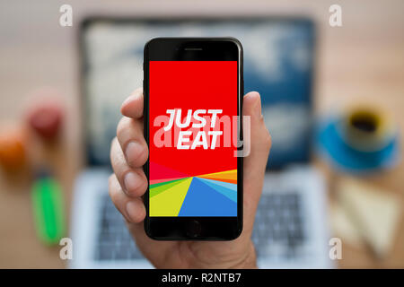A man looks at his iPhone which displays the Just Eat logo, while sat at his computer desk (Editorial use only). - Stock Photo
