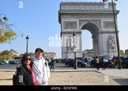 Paris, France - 2018: A couple standing during the autumn morning dusk in front at the Arc of Triomphe in Paris France - Stock Photo