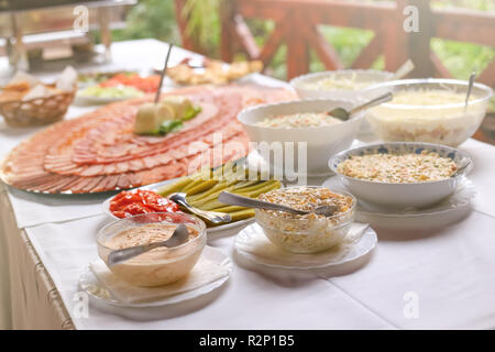 Different types of delicious salads and slices of pork dried meat on large plate. Wedding day food table. - Stock Photo