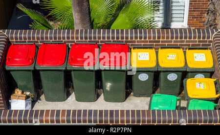 Colour coded rubbish bins, red lid for general trash, yellow lid for recyclable garbage, green lid for garden waste. - Stock Photo