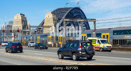 Double deck A set Waratah train and traffic on the Cahill Expressway approaching the Sydney Harbour Bridge, Sydney NSW Australia. - Stock Photo